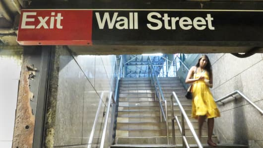 A woman walks down a staircase at the Wall Street subway station, New York City.