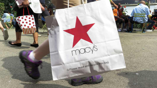 A shopper walking with a Macy's shopping bag in New York.