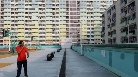 A man walks through a residential estate in Hong Kong.