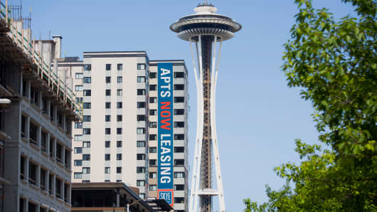 The Space Needle stands near newly constructed apartments in downtown Seattle.