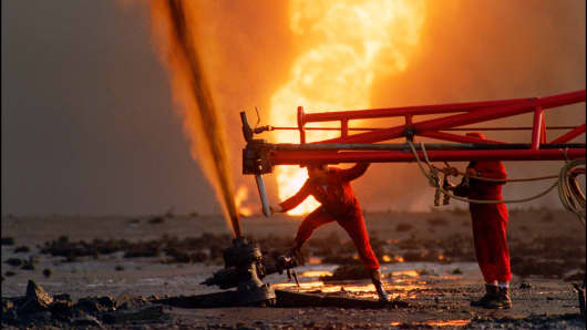 Red Adair fire fighting crew work on a blown-out well damaged by retreating Iraqi soldiers in Al-Ahmadi oil field in southern Kuwait,  March 29, 1991.