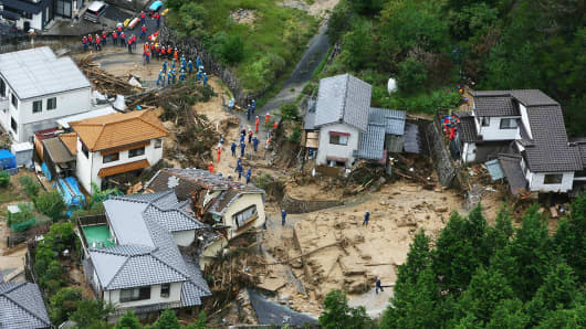 This aerial view shows policemen and rescue workers looking for survivors at a landslide site after heavy rains hit the city of Hiroshima, western Japan.