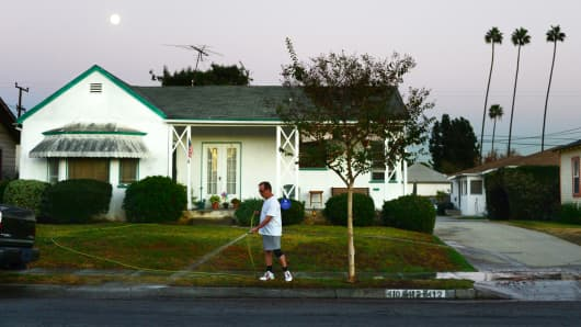 A man waters the lawn in front of his house in Monterey Park, Los Angeles County.