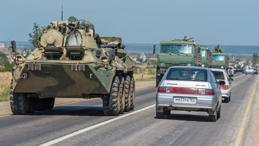 Russian armored carrier leads a column of military trucks as they leave the Ukrainian border around Kamensk-Shakhtinsky, Russia.