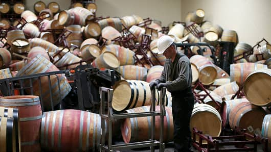 A worker cleans up barrels that collapsed in a storage room at Kieu Hoang Winery on August 25, 2014 in Napa, Calif.