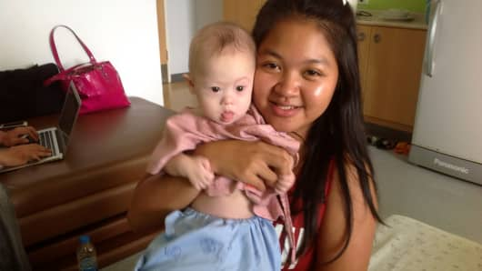 Thai surrogate mother Pattaramon Chanbua poses with baby Gammy at the Samitivej Hospital on August 6, 2014 in Chonburi province in Bangkok, Thailand.