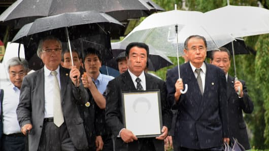 Plaintiff Mikio Watanabe (C) and his supporters enter the Fukushima district court on August 26, 2014.