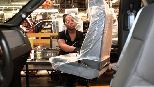 A Ford worker performs a seat install on a 2014 Ford F-150 truck at the Ford Dearborn Truck Plant, in Dearborn, Michigan.