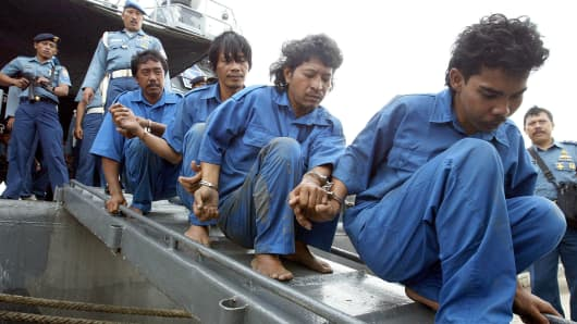 Indonesian navy sailors escort men accused of piracy, after they were arrested for attacking a Singaporean ship in Indonesia's Karimata strait from a navy ship in Jakarta's Tanjung Priok Harbor.