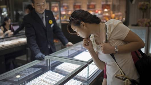 A customer looks at jewelry inside a store in Macau, China.
