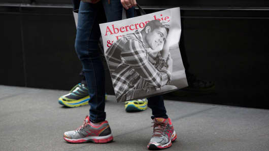 A customer carries an Abercrombie & Fitch shopping bag from a store in New York.