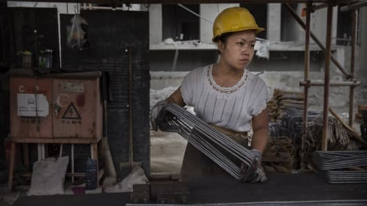 A Chinese female construction worker works at the building site of a new apartment complex in Beijing, China.