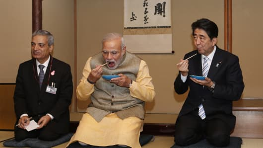 Narendra Modi and Shinzo Abe eat tea cakes during a tea ceremony in Tokyo on September 1, 2014