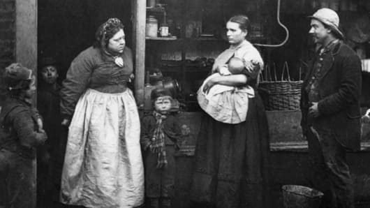 circa 1877: Impoverished people in front of a rag shop in Lambeth, London.
