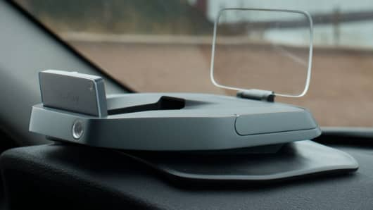 Navdy's heads-up display (HUD) mounts onto a car's dashboard and projects information onto the windshield to keep drivers from glancing down at their smartphone while driving.