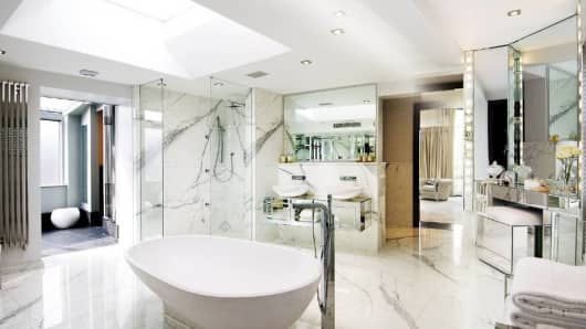 "The master bedroom has his-and-hers bathroom suites. The ""her"" bathroom, pictured here, is lined with Calacatta marble to complement the all-white interior of the bedroom."