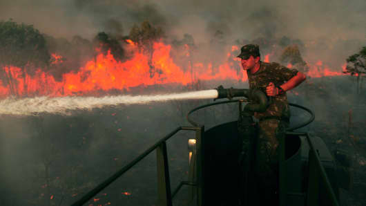 A soldier attempts to extinguish flames at the military area in Brasilia September 1, 2014. Drought, high temperatures and low humidity have caused fires to start at several places in Brasilia, according to officials.