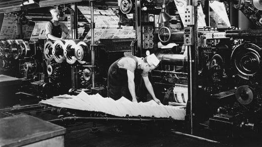 Pressmen operate a newspaper press in this circa 1940 photo.