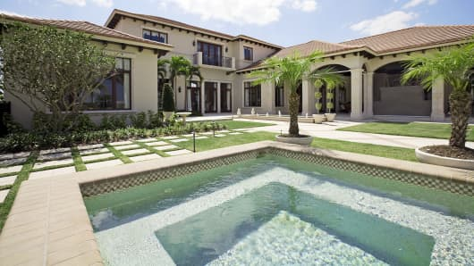 A luxury home with swimming pool is shown in Naples, Fla.