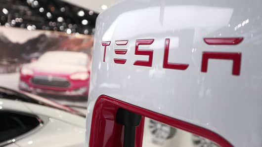 The Tesla Motors logo is seen on a charging station at the company's booth during the 2014 North American International Auto Show Detroit.