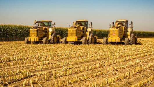 Three farm tractors in a freshly cut cornfield near Visalia, California.