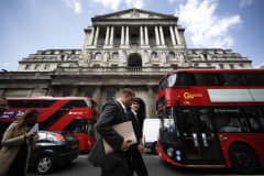 Businessmen pass red buses outside the Bank of England in London.