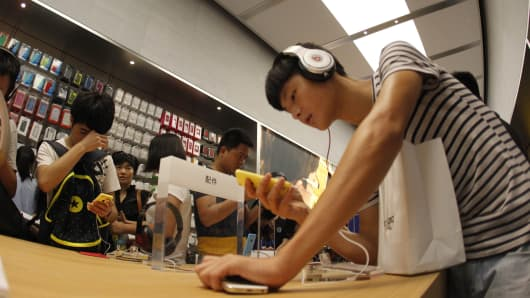 A man experiences Apple's products at Chongqing's first Apple direct-sale store in Chongqing, China.