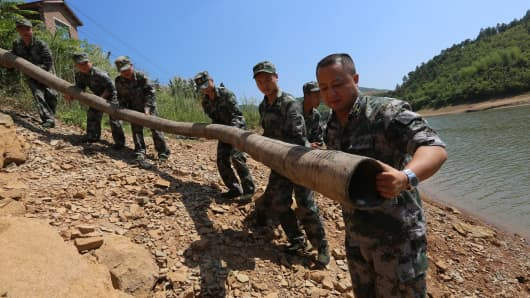 Soldiers help villagers with a pipe line to pump water from a pond at Pingdi village in Loudi, China.