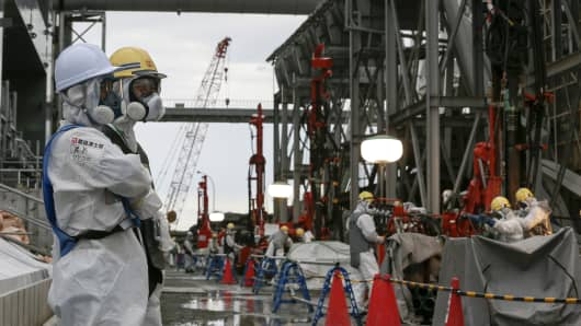 Workers wearing protective clothing and masks watch their colleagues at the building site for a frozen underground wall surrounding the crippled reactor buildings at Tokyo Electric Power Co.'s (Tepco) Fukushima Dai-ichi nuclear power plant in Okuma, Fukushima Prefecture, Japan.