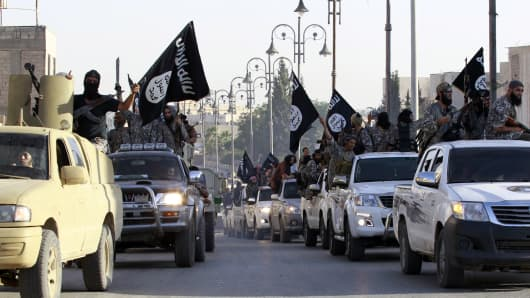 Militant Islamist fighters parade on military vehicles along the streets of northern Raqqa province, June 30, 2014.