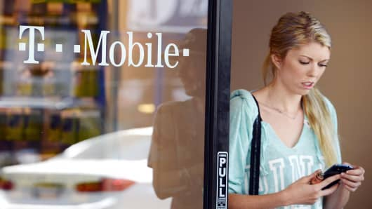 A customer exits a T-Mobile store in Glendale, Calif.
