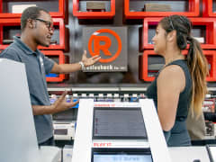 RadioShack employee demonstrating interactive speaker wall
