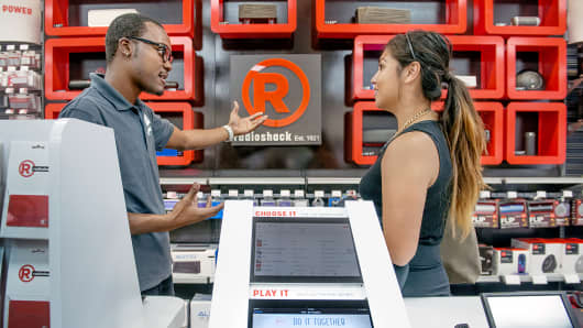 Employee Raymond Stevens demonstrates to a customer how she can try out speakers using a tablet at a RadioShack store in Washington, Sept. 8, 2014.