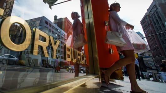 A customer leaves a Tory Burch store on Madison Avenue in New York, Sept. 3, 2014.