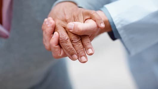 Doctor holding elderly hand