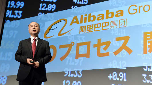 SoftBank CEO Masayoshi Son speaks in front of a screen displaying the Alibaba Group logo during a news conference in Tokyo.