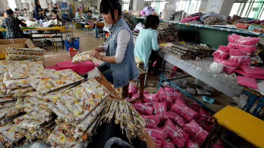 Workers at a handbag factory completing orders to be sold through the Chinese internet e-commerce site Taobao a division of Alibaba.