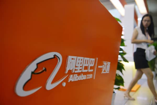 A woman walking past the Alibaba booth during an exhibition in Hangzhou, China.