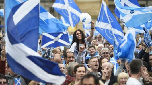 Campaigners wave Scottish Saltires at a 'Yes' campaign rally in Glasgow, Scotland September 17, 2014.