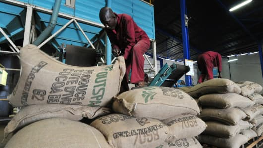 Employees of a cocoa export company pile up sacks in a packaging factory in the Ivory Coast.