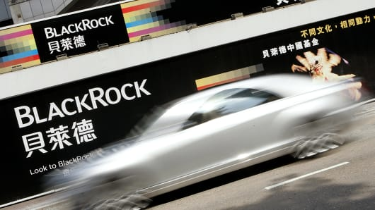 A car drives past a BlackRock billboard ad in Hong Kong.
