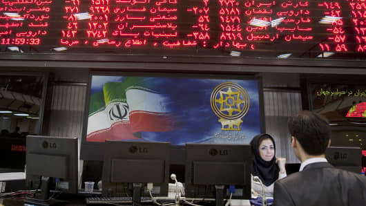 A trader speaks with a stock market official beneath the electronic board at the Tehran Stock Exchange, Sept. 15, 2010.