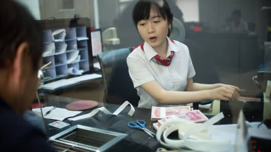 A worker at a branch of ICBC counts money as she serves a customer.