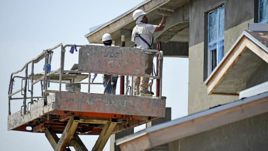 Workers apply stucco at a housing development under construction in Jupiter, Fla.