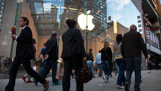 Pedestrians walk by an Apple store in New York.