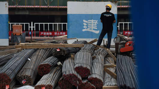 A worker stands on reinforcing steel at a construction site in Beijing, China.