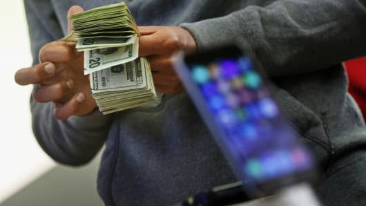 A customer counts cash at an Apple store in New York.