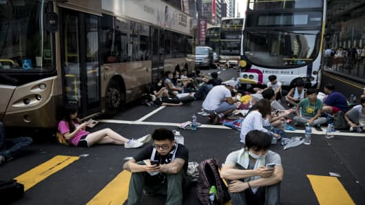 Pro-democracy protesters rest around empty buses as they block off Nathan Road, a major route through the heart of the Kowloon district of Hong Kong.