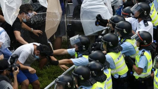 Riot police use pepper spray as they clash with protesters, as tens of thousands of protesters block the main street to the financial Central district outside the government headquarters in Hong Kong September 28, 2014.