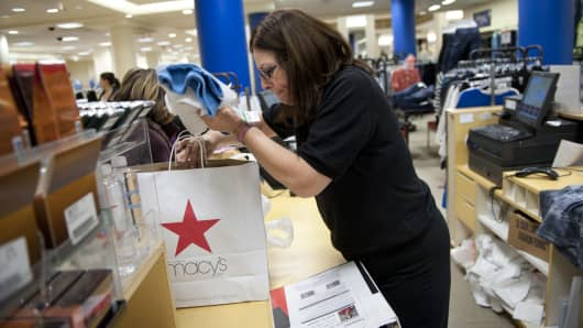 A Macy's employee helps a customer at a Macy's store in Chicago. Macy's is expected to hire more workers this holiday season.